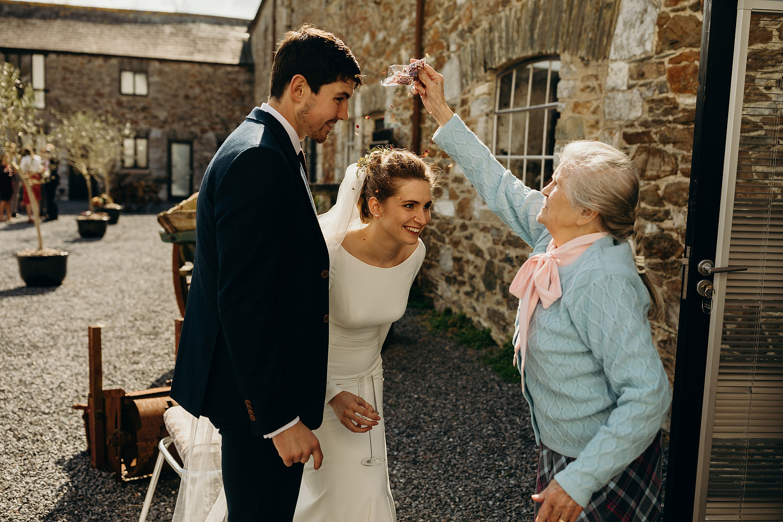 grandmother throws confetti on bride