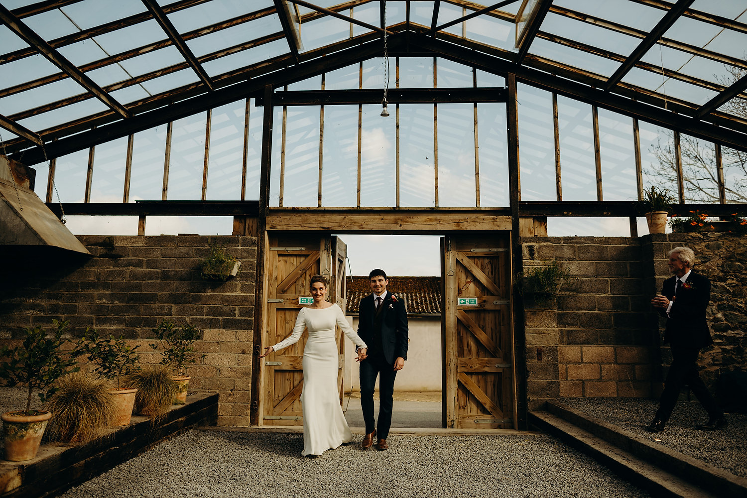 bride and groom walk into glasshouse for reception