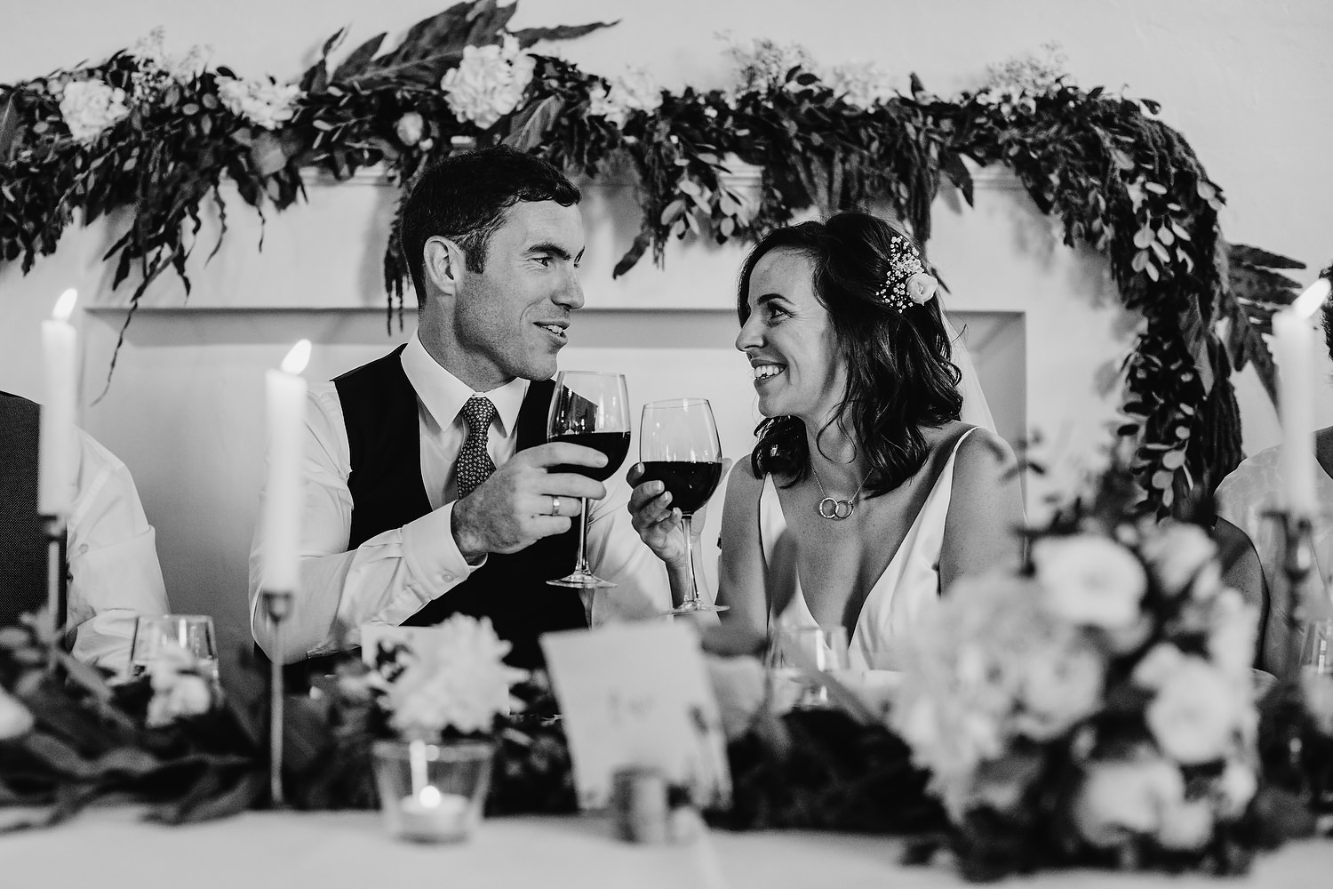 couple raise glass as looking at each other