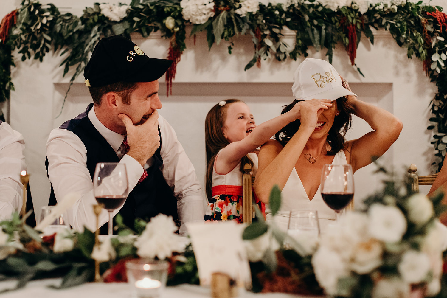 girl putting a hat on bride