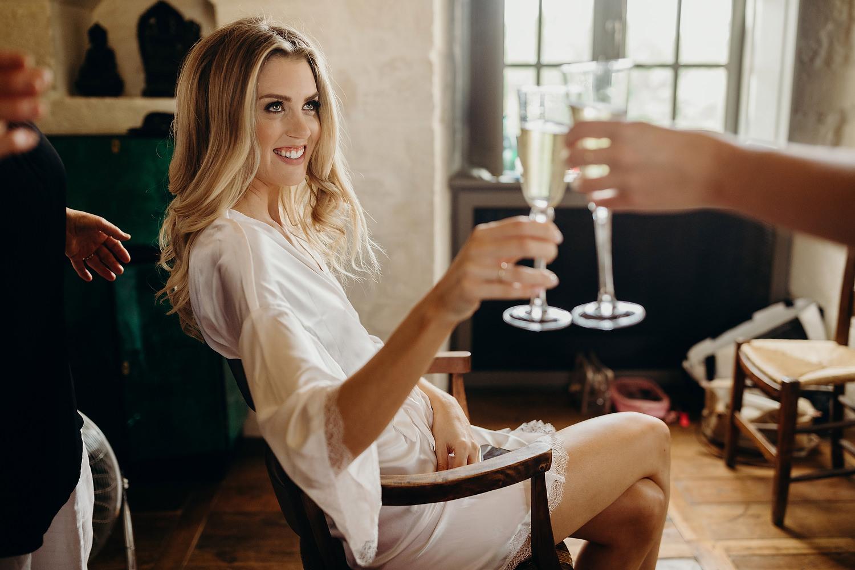 bride raises champagne glass