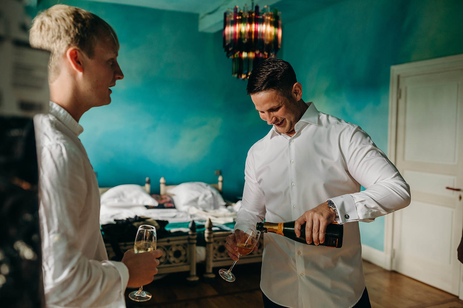 groom pours champagne during morning of wedding