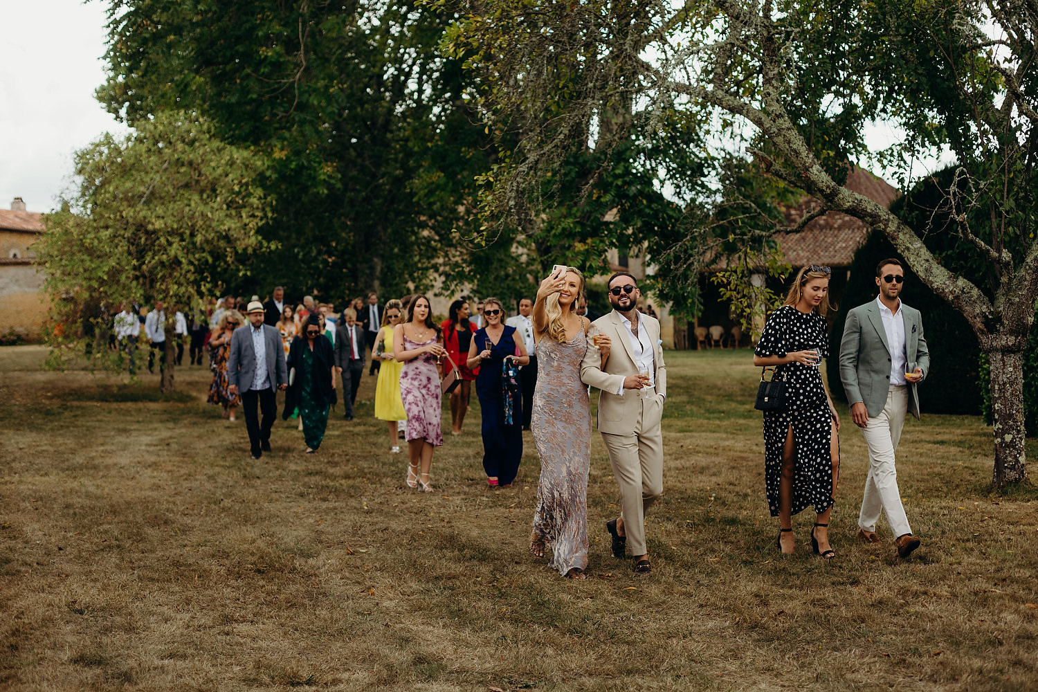 guests walk to outdoor french ceremony