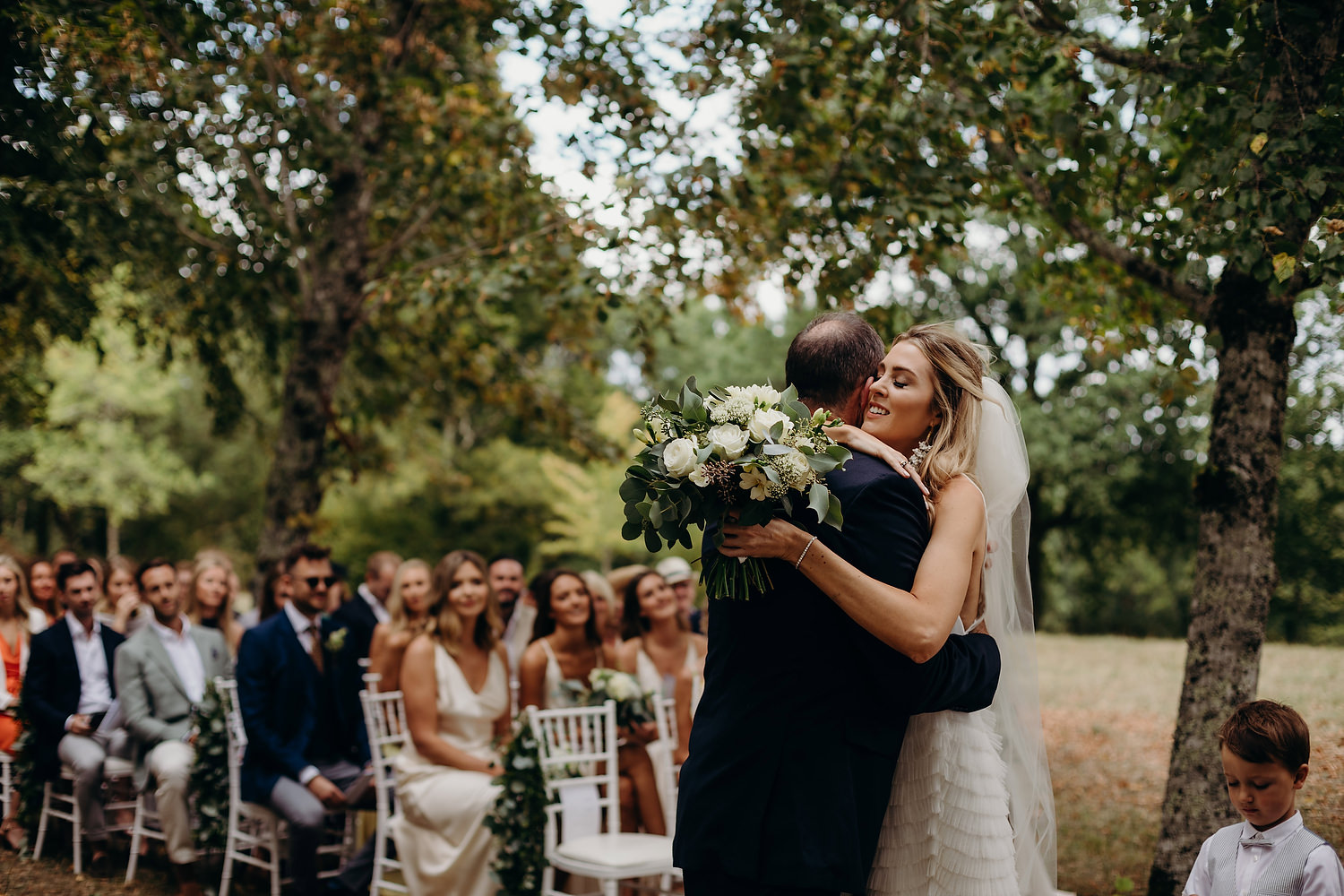 Bride hugs father during ceremony