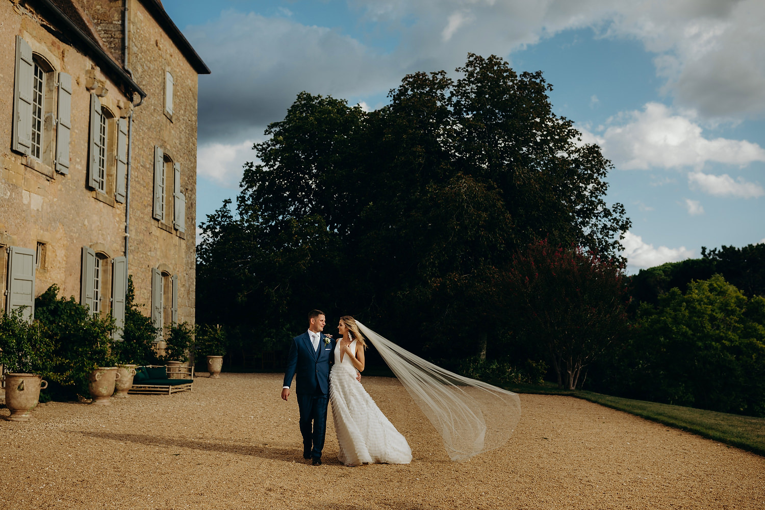 veil blowing in the wind as couple walk