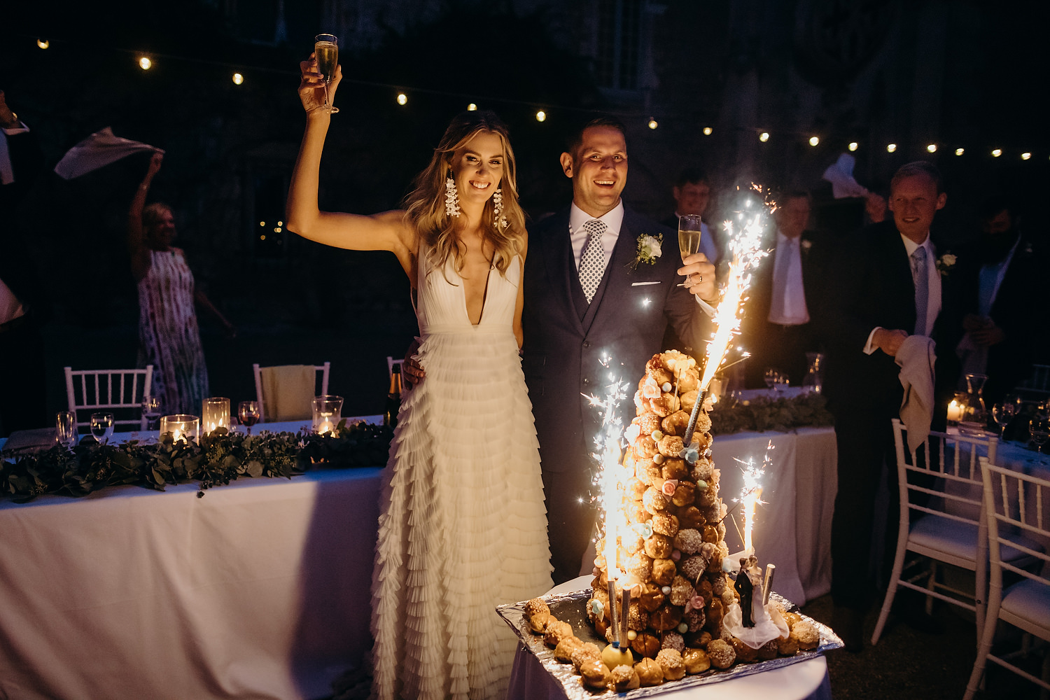 bride and groom with large wedding cake sparklers