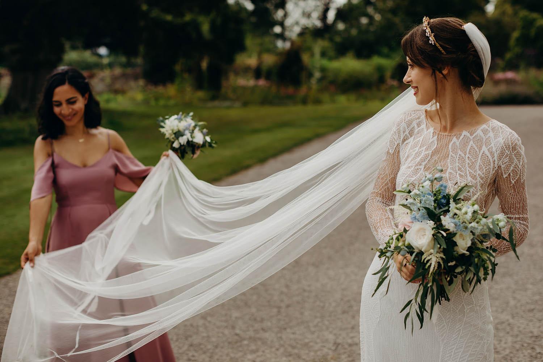 Bridesmaid spreading veil