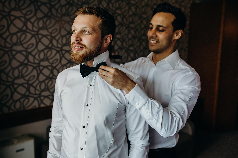 groom getting bow tie on