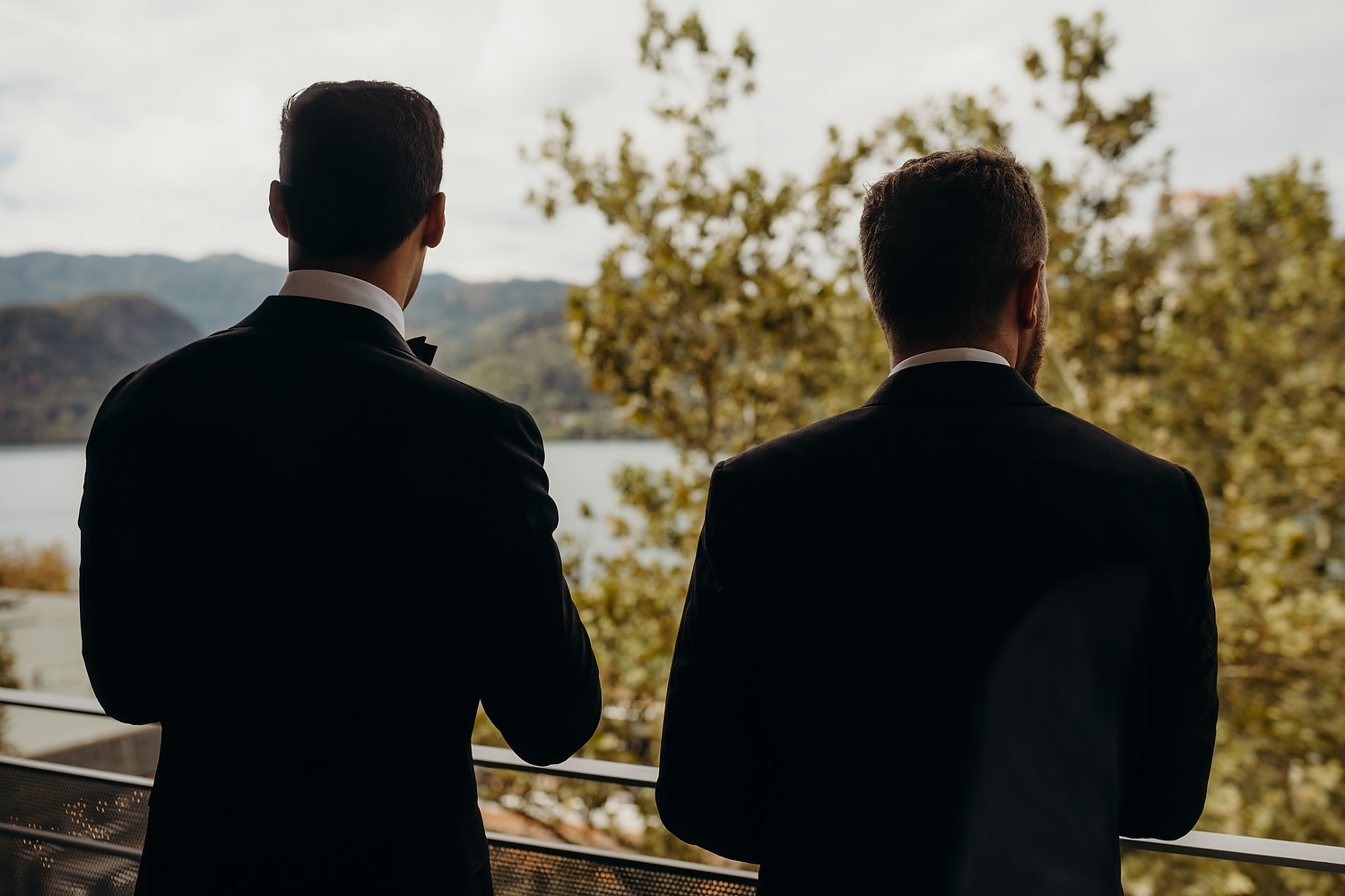 Groom and best man take in lake view