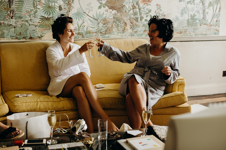 bride sharing drink with bridesmaid