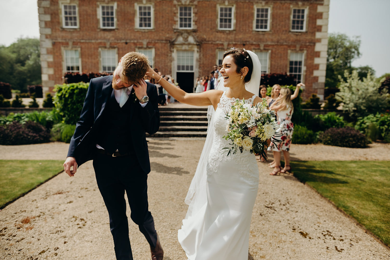 bride shaking confetti off groom
