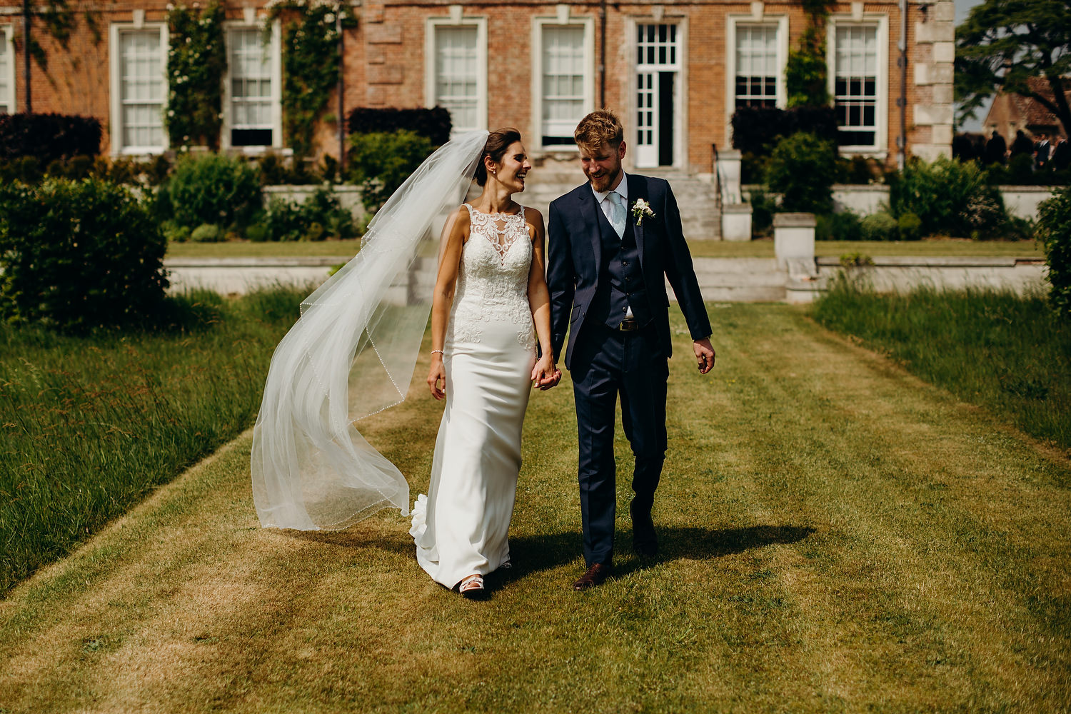 bride and groom walking on grounds of estate